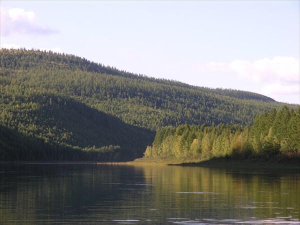 Покатые горушки сжимают реку.