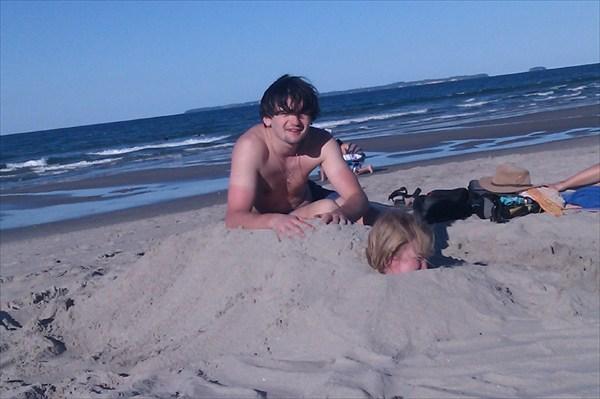 Закопанная в песок Оля