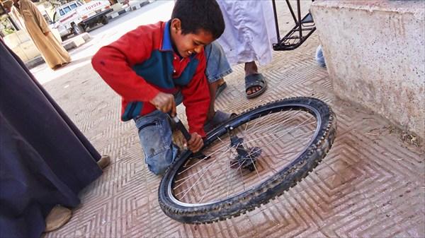 Мальчик помогает накачать колесо