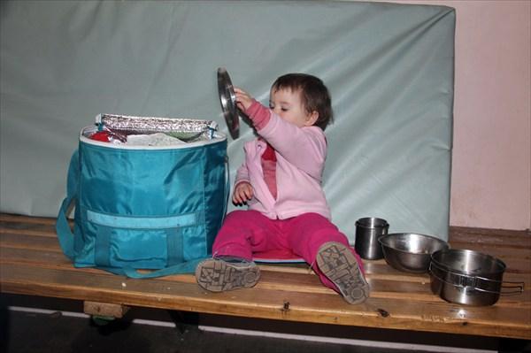 Тая помогает складывать кастрюльки и крышки в продуктовую сумку