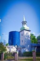 """""""Казанская церковь"""" 1721 года постройки на фоне офисного центра."""
