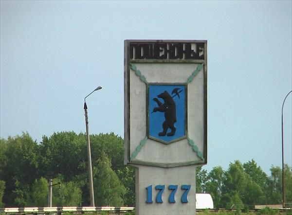 на фото: Герб города на въезде