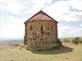 Маленький храм, около него сидят пограничники