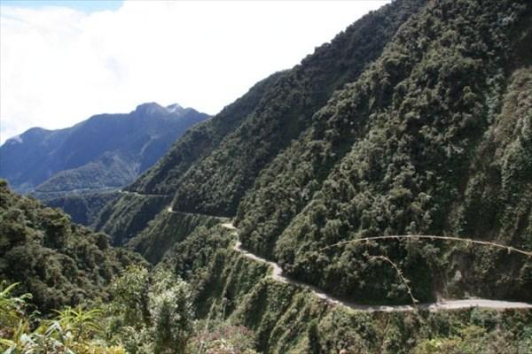 на фото: дорога идет через горы,среди джунглей.