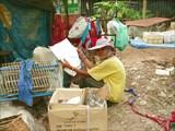 Невозмутимая старуха читает газету,сидя на куче мусора.