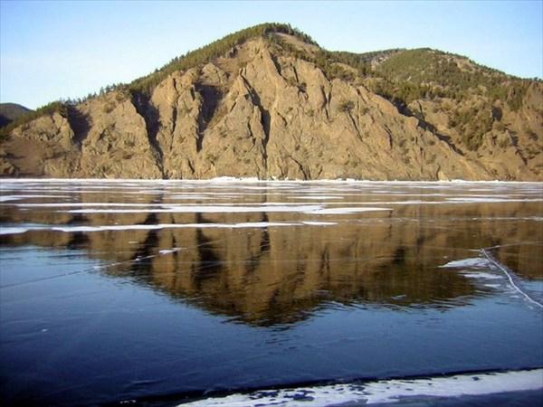 на фото: Высокий берег отражается в застывшей воде как в зеркале
