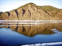 Высокий берег отражается в застывшей воде как в зеркале