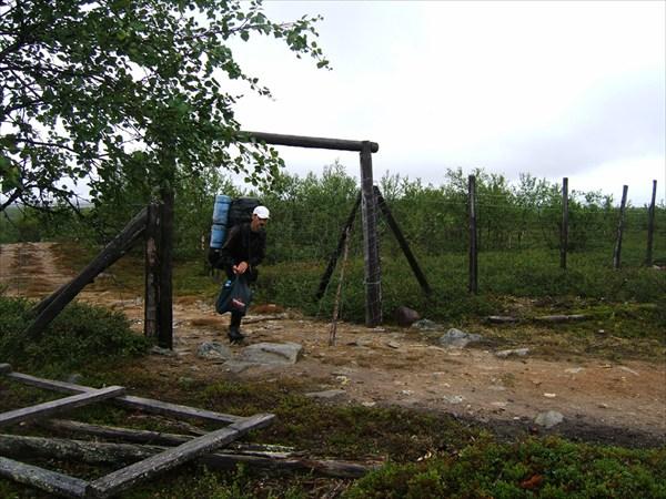 Мой спутник Шура проходит через ворота оленьего забора