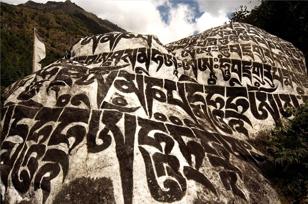 Гигантские символы мантры, высеченные на скале