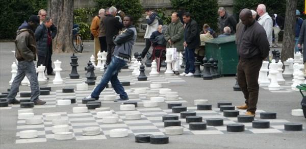…Чёрные люди гоняют шашки (причем, не вынимая рук из карманов):
