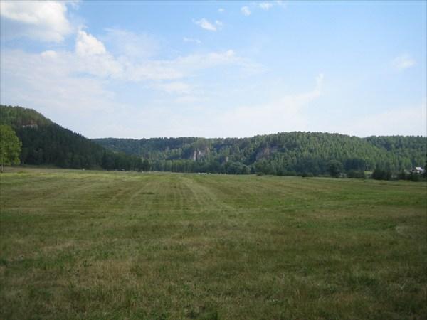 Скошенный луг, вдалеке виден палаточный лагерь