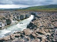 Ледниковая речка течет через застывшую лаву
