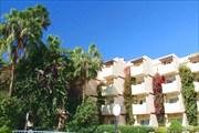 Вид на отель Odyssee Park Hotel c лежака у бассейна