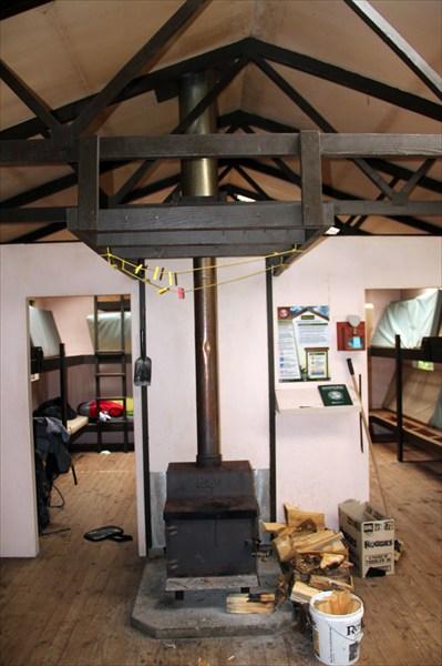 Внутри печь с дровами и две комнаты с 2-3-этажными кроватями