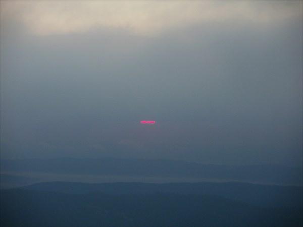 Солнце выглядывает в щёлочку между горизонтом и облаками